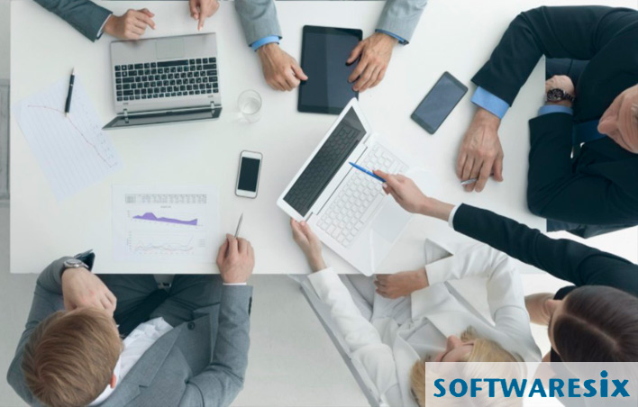 Business people in a meeting, using multiple devices to plan hub site organization